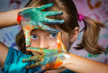 IMAGE: Young white girl with painted hands.
