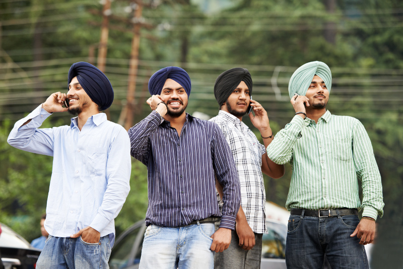 IMAGE: Four young Indian Sikh men in turbans talking on mobile phones.