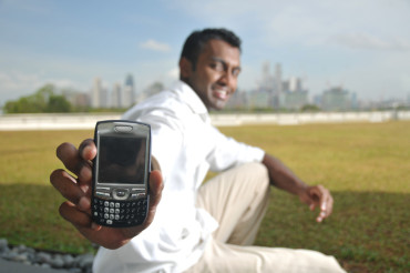 IMAGE: Indian Man dressed in white shirt and khaki pants smiles as he holds out his feature phone.