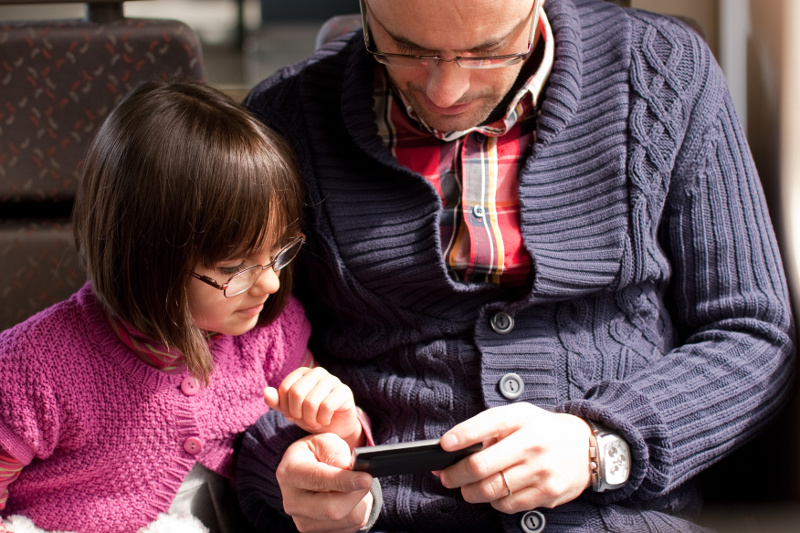 IMAGE: Father and daughter with glasses watching a video on a smartphone while travelling by train.
